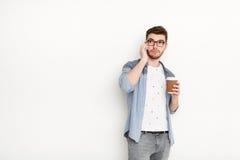 Ung upptagen man som talar på telefonen med coffeecup Fotografering för Bildbyråer