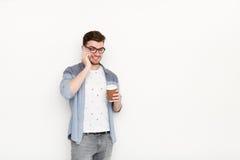 Ung upptagen man som talar på telefonen med coffeecup Arkivfoton