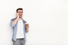 Ung upptagen man som talar på telefonen med coffeecup Royaltyfri Fotografi