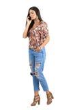 Ung upptagen tillfällig kvinna som talar på mobiltelefonen, medan gå Arkivfoton