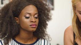 Ung ursnygg svart afrikansk amerikanaktris som får klar för att filma Sminkkonstnär som applicerar sminket för svart arkivfilmer