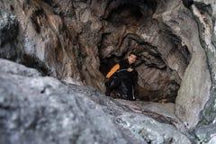 Ung utforskare i svart sportswear i en grotta med klättringutrustning som är klar för handling royaltyfria foton
