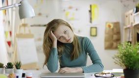 Ung utmattad kvinna som ser till kameran vid tabellen arkivfilmer