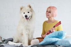 Ung vänlig glad flicka som spelar ukulelet, gitarrsittien fotografering för bildbyråer