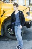 Ung väntande på buss för tonårs- pojke som hem går Arkivbilder