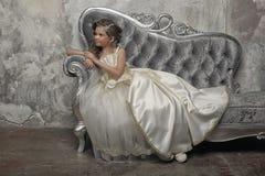 Ung viktoriansk prinsessa som sitter på en silversoffa royaltyfria bilder