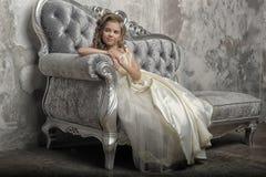 Ung viktoriansk prinsessa som sitter på en silversoffa royaltyfri bild