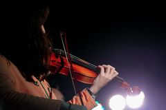 Ung violinist Girl Performance med hennes fiolinstrument p? den inomhus konsertetappen royaltyfri foto