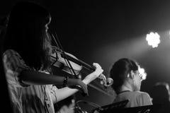 Ung violinist Girl Performance med hennes fiolinstrument p? den inomhus konsertetappen svart white royaltyfri fotografi
