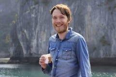 Ung vit attraktiv blond man med ett skägg i en blå grov bomullstvillskjorta som defiantly skrattar med ett exponeringsglas av kaf royaltyfria foton