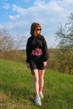 Ung vit flicka med kinesiobandet p? hennes buk och ben utomhus i v?r arkivbild
