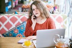Ung vit flicka med rött lockigt hår som talar på telefonsammanträdet på en tabell med en bärbar dator i ett kafé Allvarligt förbr fotografering för bildbyråer