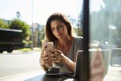 Ung vit kvinna som använder smartphonen på en tabell utanför ett kafé Royaltyfri Bild