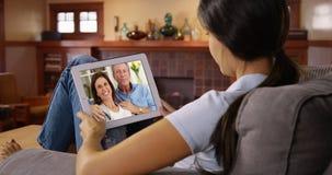 Ung vit kvinna som talar till hennes föräldrar via video pratstund arkivfoto