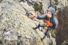 Ung vit man som klättrar en brant vägg i bergen som klättrar extrema sportar, horisontalriktning för bred vinkel arkivfoton