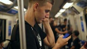 Ung vuxen Caucasian man som rider ett tunnelbanagångtunneldrev och smsar på hans mobiltelefon 4K arkivfilmer