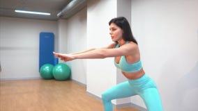 Ung vuxen flicka som gör övningar i idrottshallen stock video
