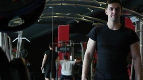 Ung vuxen idrotts- man i sportar som beklär att hydratisera från en kulör plast- vattenflaska på idrottshallen under en crossfit stock video