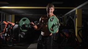 Ung vuxen kroppsbyggare för motivation som gör att lyfta för vikt i idrottshall lager videofilmer