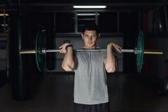 Ung vuxen kroppsbyggare som gör att lyfta för vikt i idrottshall Arkivfoto