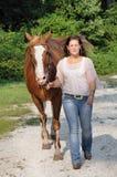 Ung vuxen kvinna som går henne häst Arkivfoto