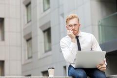 Ung vuxen ljust rödbrun skäggig affärsman, arbete i dator och drömma arkivfoton
