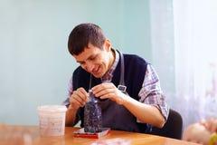 Ung vuxen man med handikappet som är förlovat i hantverk på praktisk kurs, i rehabiliteringmitt royaltyfri foto