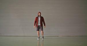 Ung vuxen man som bär den med huva tröjan under konditionsportgenomkörare Slapp fokus Industriell stads- utbildning för Grunge 4K lager videofilmer