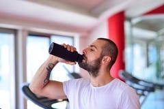 Ung vuxen man som dricker flaskan av vatten på trreadmill i idrottshall Royaltyfri Foto