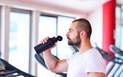 Ung vuxen man som dricker flaskan av vatten på trreadmill i idrottshall Royaltyfri Bild