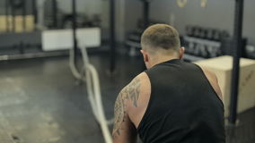 Ung vuxen man som gör crossfitgenomkörare med ledde rep stock video