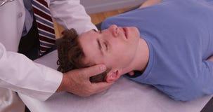 Ung vuxen man som har halsskadan att undersökas av kiropraktorn arkivbilder