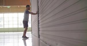 Ung vuxen man som värmer sträckning under konditionsportgenomkörare upp Slapp fokus Industriell stads- utbildning för Grunge 4K s lager videofilmer