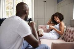 Ung vuxen svart kvinna som sitter på en soffa som dricker kaffe som ler på hennes partner, selektiv fokus royaltyfri foto