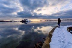 Ung vuxen tyckande om solnedgång och den trevliga reflexionen av ön in Arkivfoton