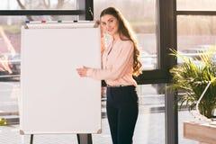 Ung whiteboard för blanko för affärskvinnadanandepresentation och se kameran Royaltyfri Fotografi