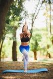 Ung yoga för yogakvinnapraktiker på naturen bakgrundsblurblomma inom som looks s arkivbild