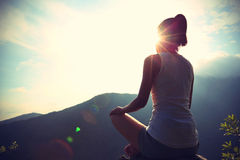 Ung yogakvinna på soluppgångberget Arkivbild