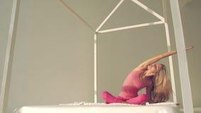Ung yogakvinna som bär rosa sporttorkdukar som gör yoga i säng stock video