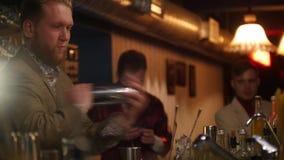 Ung yrkesmässig bartender som häller och skakar en drink i stången med mjuk inre belysning arkivfilmer