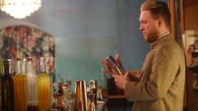 Ung yrkesmässig bartender som häller och skakar en drink och skrattar i inre flott stång med mjuk inre belysning stock video