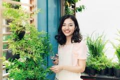 Ung yrkesmässig kvinna i nagelsax för buske för förklädesnittgräsplan i Fotografering för Bildbyråer