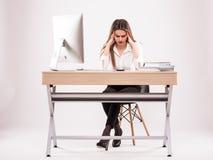 Ung yrkesmässig kvinna som är stressad och som är trött med huvudvärksammanträde på kontorsskrivbordet på vit royaltyfria bilder