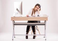 Ung yrkesmässig kvinna som är stressad och som är trött med huvudvärksammanträde på kontorsskrivbordet på vit bakgrund royaltyfri bild
