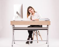 Ung yrkesmässig kvinna som är stressad och som är trött med huvudvärksammanträde på kontorsskrivbordet på vit bakgrund royaltyfria bilder