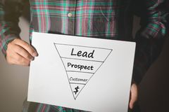 Ung yrkesmässig man som rymmer ett försäljningstrattdiagram på ett vitt ark av papper arkivfoton