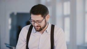 Ung yrkesmässig säker manlig chef som framlägger projekt till kollegor, ler och talar i modernt ljust kontor stock video