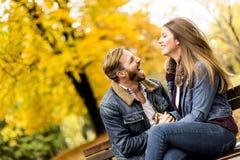 Unga älska par på en bänk i höst parkerar Arkivfoto
