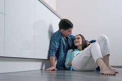Unga älska par på parkettgolvet i inre sammanträde för vitt kök och le på de royaltyfri bild
