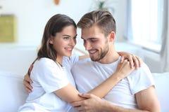 Unga älska par på tv och att skratta för soffa hemmastadd hållande ögonen på royaltyfria bilder